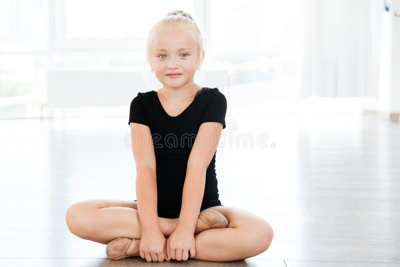 La bailarina de la niña que se sentaba con las piernas cruzó en estudio del ballet foto de archivo libre de regalías