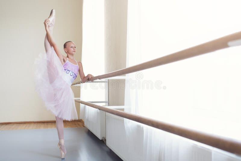 La bailarina en el tutú que estiraba la pierna en vertical partió en clase foto de archivo