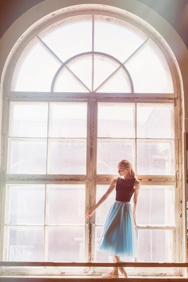 La bailarina está presentando delante de una ventana grande fotos de archivo libres de regalías