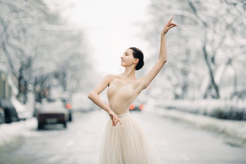 La bailarina hermosa está bailando en la calle de la ciudad nevosa entre los coches foto de archivo