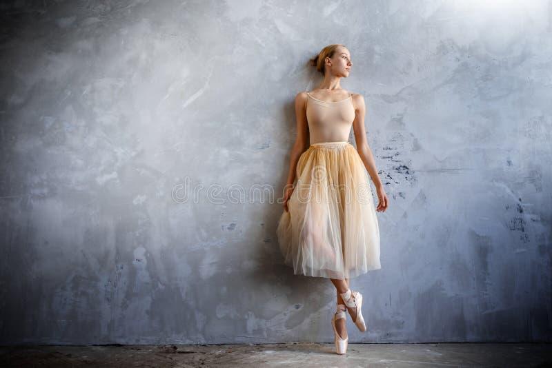 La bailarina joven en un traje de baile coloreado de oro está presentando en un estudio del desván imagen de archivo