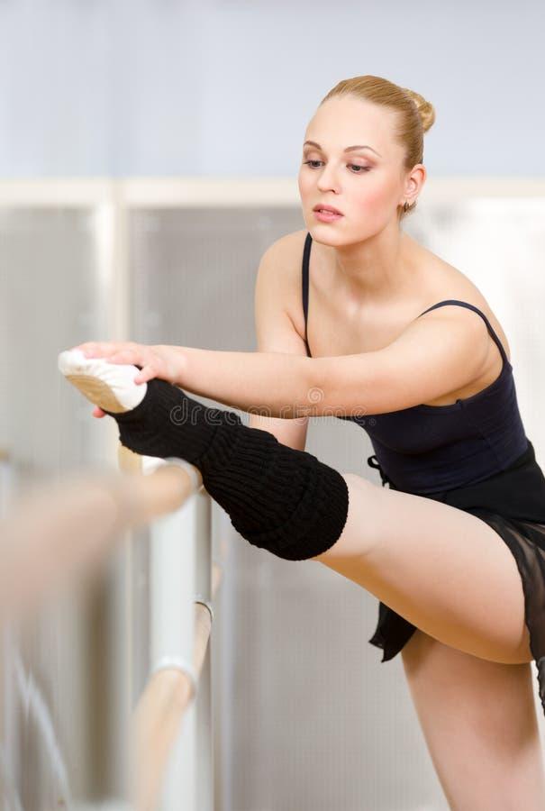 La bailarina se estira usando la barra imagen de archivo