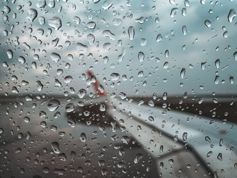 La baisse de pluie à la fenêtre d'avion décollent avant quand saison de mousson photographie stock libre de droits