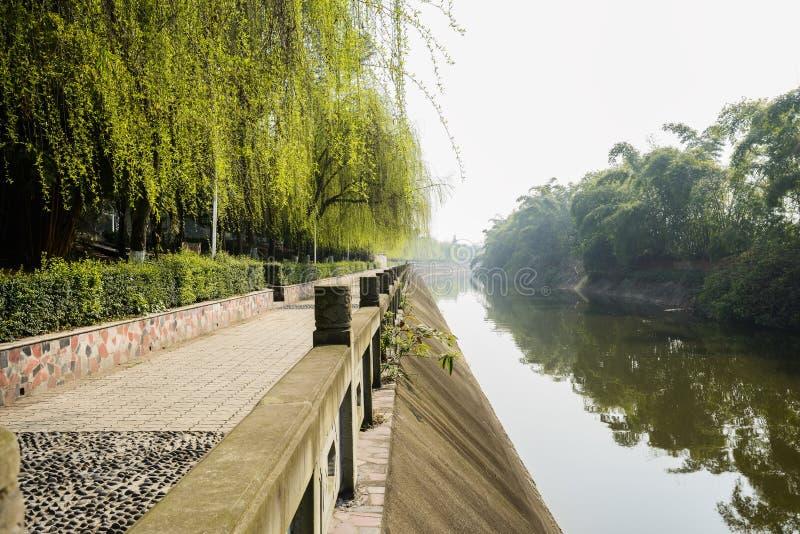 La balaustra di pietra ha recintato la pavimentazione della riva del fiume in molla soleggiata fotografie stock libere da diritti