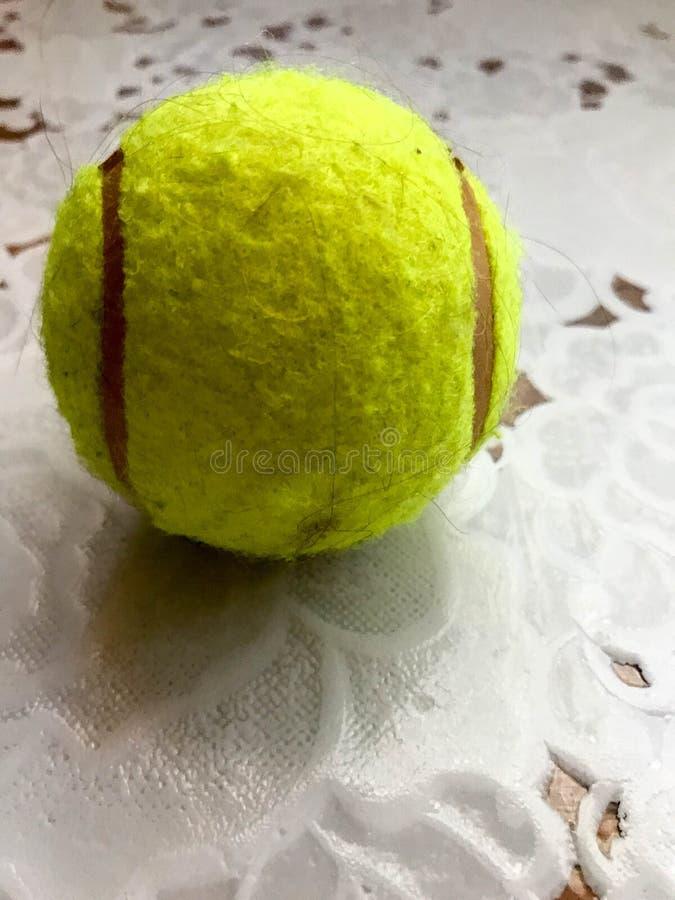 La balle de tennis pelucheuse jaune pour jouer le tennis se trouve sur une table sur le fond d'une nappe blanche photographie stock