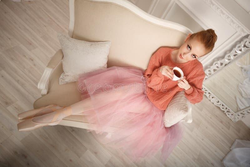 La ballerina che beve il tè nero e si rilassa fotografia stock