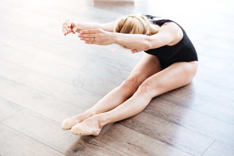 La ballerina graziosa della giovane donna che si siede e che fa l'allungamento si esercita fotografia stock