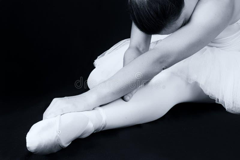 La ballerina si siede sul pavimento per mettere sopra le pantofole immagine stock libera da diritti