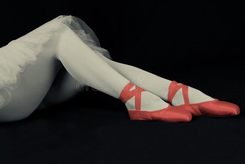 La ballerina si siede sul pavimento per mettere sopra le pantofole prepara al perfor fotografie stock