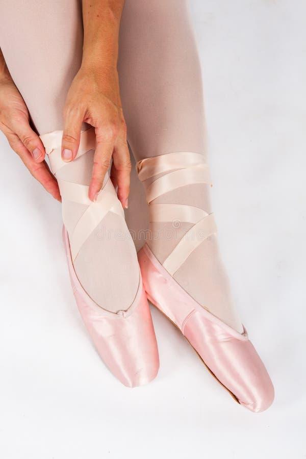 La ballerina si siede sul pavimento per mettere sopra le pantofole prepara per la perforazione fotografie stock