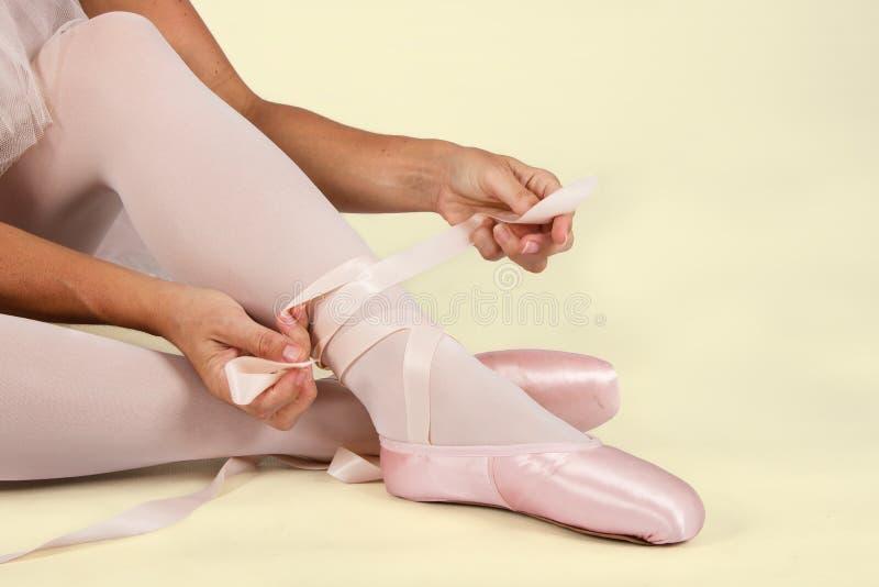 La ballerina si siede sul pavimento per mettere sopra le pantofole prepara per la perforazione immagini stock libere da diritti