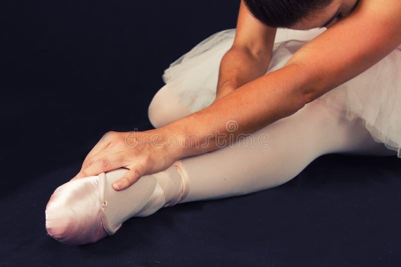La ballerina si siede sul pavimento per mettere sopra le pantofole prepara per la perforazione fotografia stock