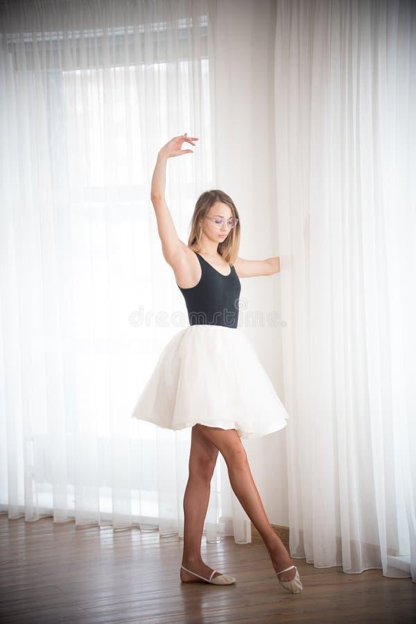 La ballerina sta stando in una posa del ballo, in uno studio luminoso immagini stock libere da diritti