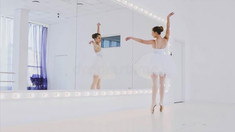 La ballerina in tutu bianco sta praticando gli elementi di ballo davanti allo specchio fotografie stock libere da diritti