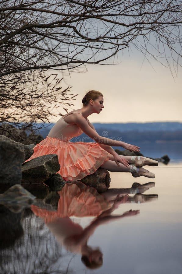 La ballerine dans la pose de ballet s'assied au-dessus du lac sur le fond de la SK photo libre de droits