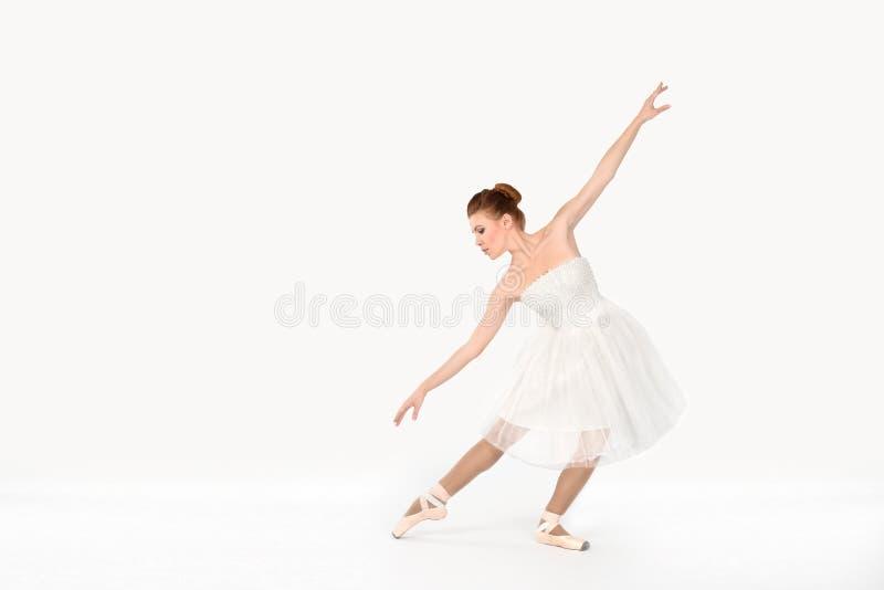 La ballerine dans les pointes et une robe danse sur un backgroun blanc image stock
