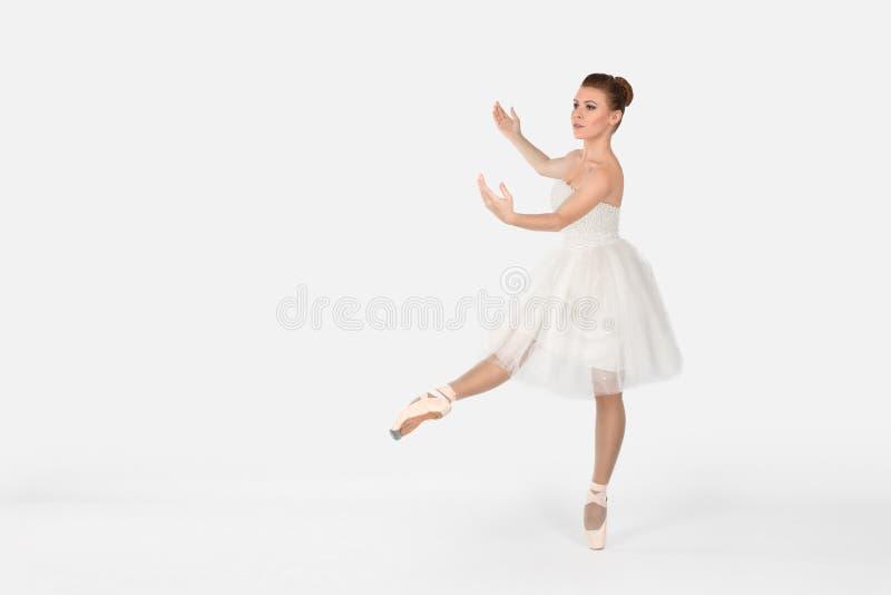 La ballerine dans les pointes et une robe danse sur un backgroun blanc images stock