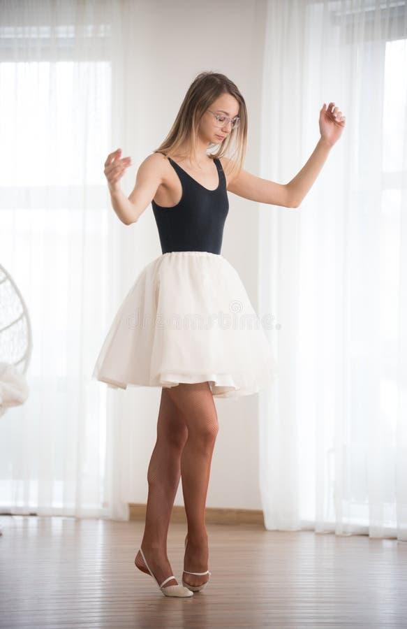 La ballerine en verres se tient sur la pointe des pieds pendant l'après-midi dans le studio de danse photographie stock libre de droits