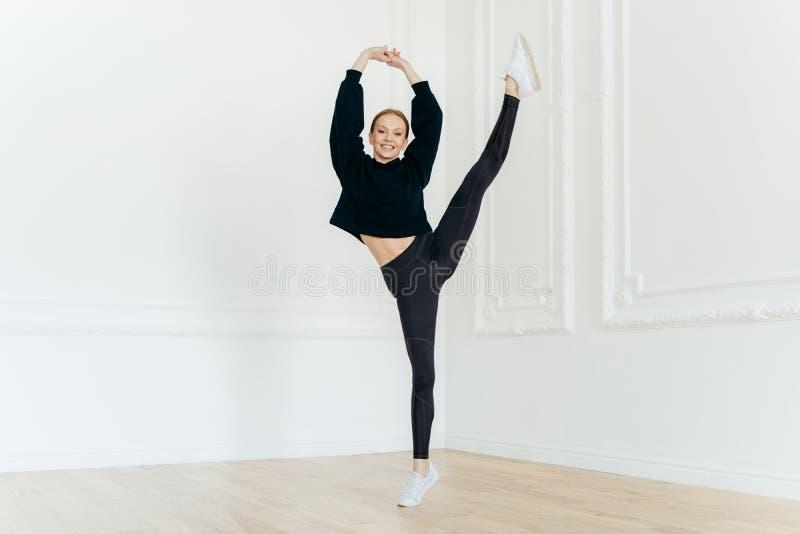 La ballerine féminine flexible sportive soulève des mains, équilibre sur une jambe, a l'expression du visage gaie, étant dans la  photos stock