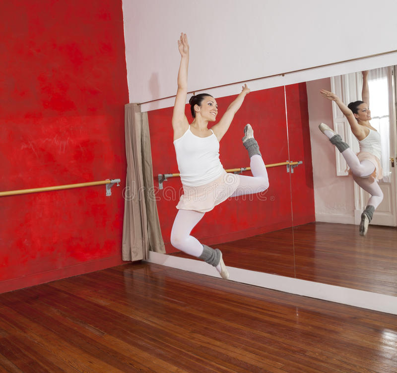 La ballerine sautant tout en exécutant dans le studio de danse photographie stock libre de droits