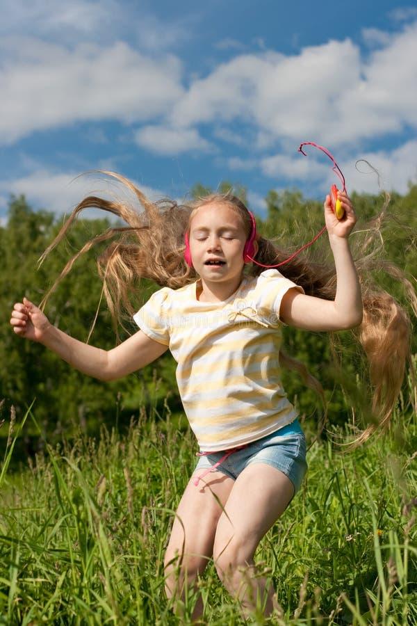 La bambina è ballare esterno in cuffie immagini stock libere da diritti