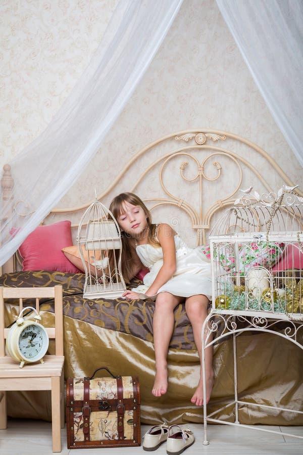 La bambina è caduto addormentato mentre si sedeva sul letto immagine stock libera da diritti