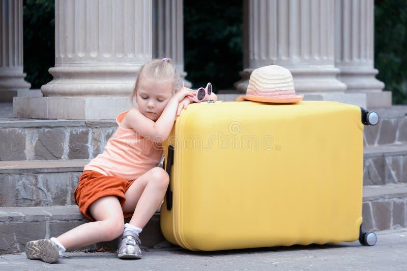 La bambina è caduto addormentato su una grande valigia gialla Un bambino sveglio è stanco del viaggio fotografie stock libere da diritti