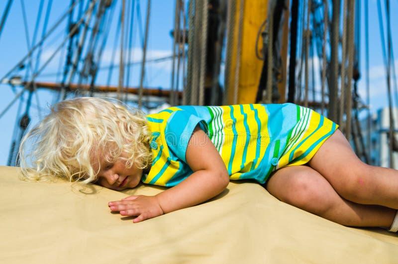 La bambina è caduto addormentato sulla piattaforma di una barca a vela immagine stock