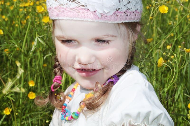 La bambina è fra i fiori gialli immagine stock libera da diritti