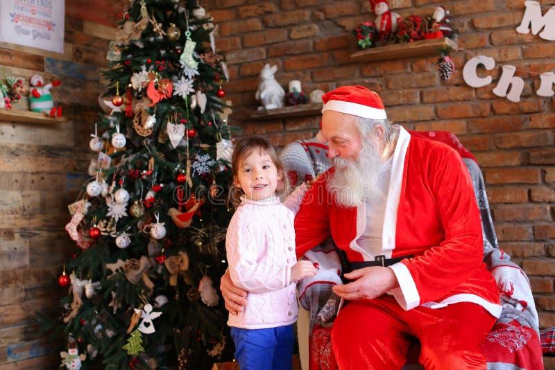 La bambina abbraccia Santa Claus e fa il desiderio per il Natale nel coz immagine stock libera da diritti