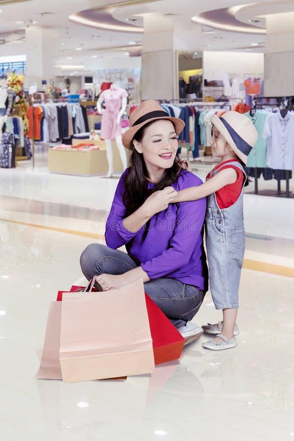 La bambina abbraccia sua madre nel centro commerciale fotografia stock libera da diritti