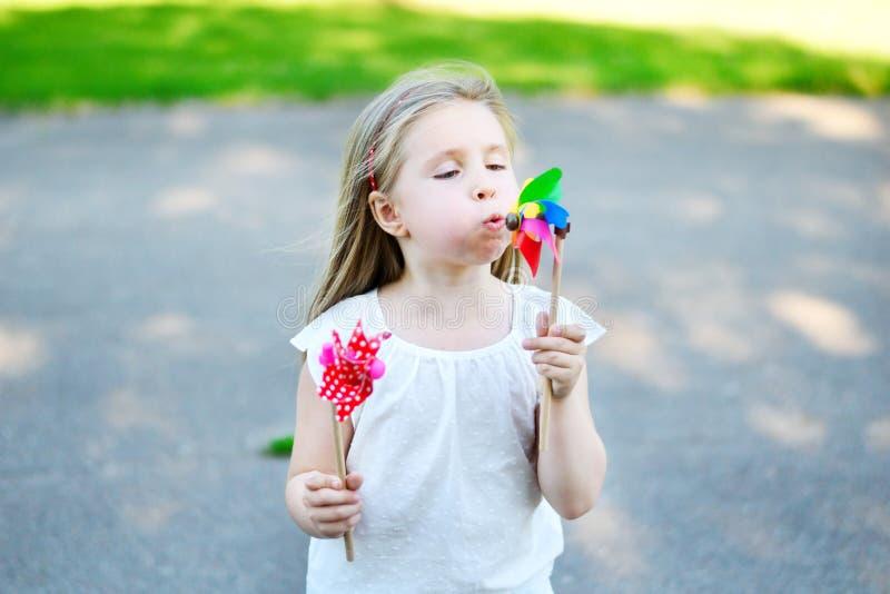 La bambina adorabile nel giorno di estate giudica il mulino a vento disponibile fotografia stock