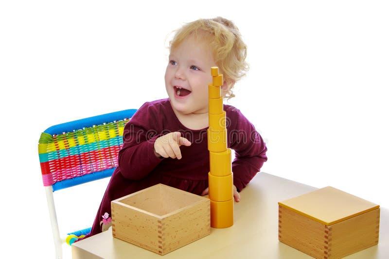 La bambina agli impianti della tavola con il materiale di Montessori immagine stock libera da diritti
