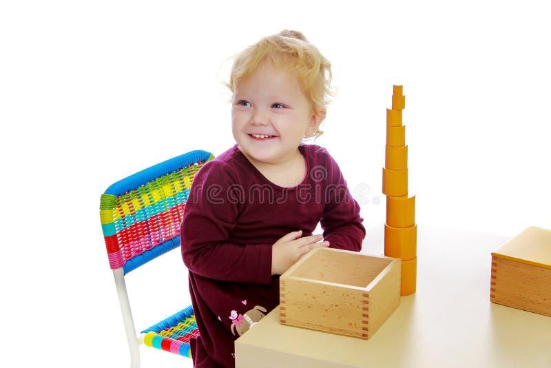 La bambina agli impianti della tavola con il materiale di Montessori fotografia stock libera da diritti