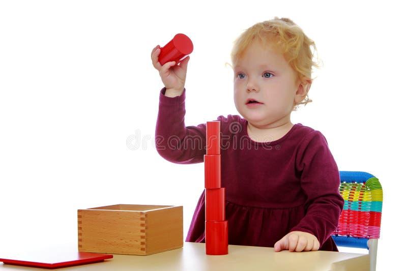 La bambina agli impianti della tavola con il materiale di Montessori immagine stock