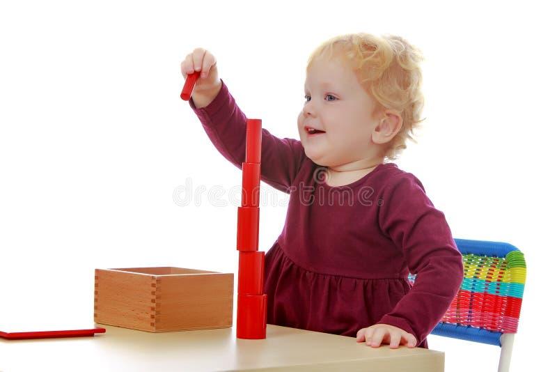 La bambina agli impianti della tavola con il materiale di Montessori fotografie stock