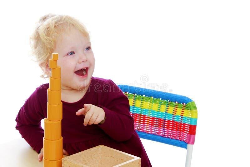 La bambina al tavolo lavora con il materiale Montessori immagini stock