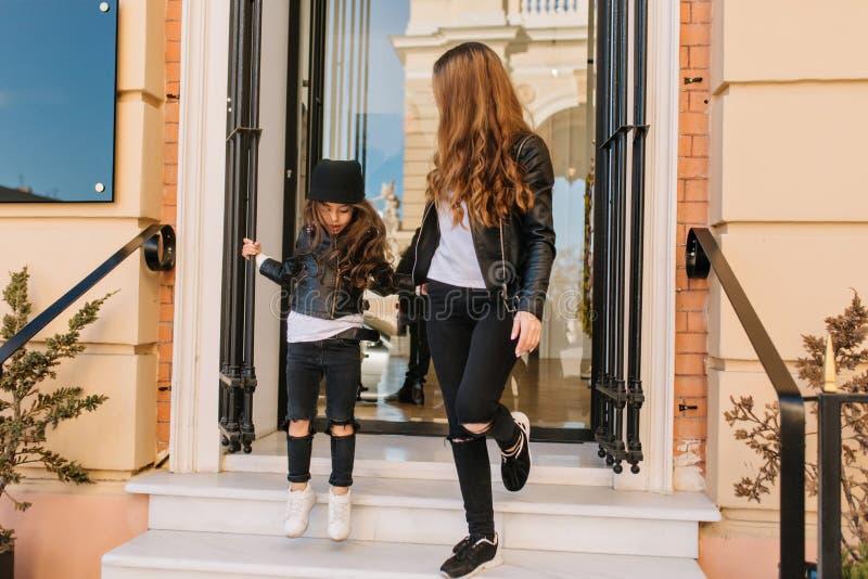 La bambina alla moda che porta i jeans e scarpe da tennis bianche esce da coprire il deposito che tiene la mano della madre Ritra fotografie stock libere da diritti