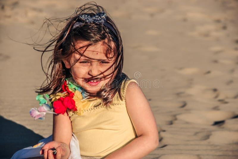 La bambina alla spiaggia, ragazza del bambino vestita l'estate posa molto bene sulla sabbia fotografia stock libera da diritti