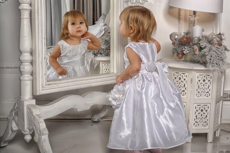 La bambina ammira la sua riflessione in specchio fotografie stock