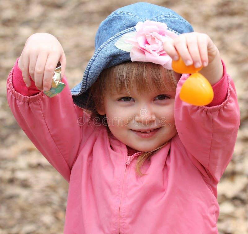 La bambina apre l'uovo di Pasqua Per la caramella fotografie stock