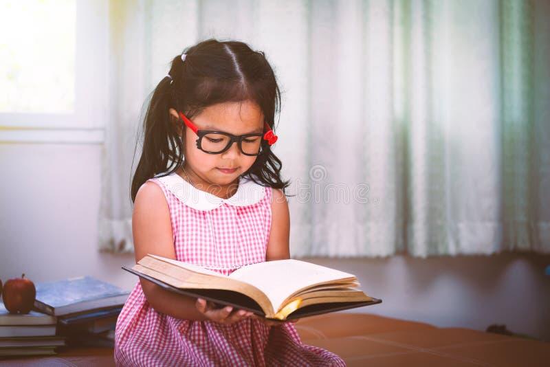 La bambina asiatica del bambino ha messo sopra gli occhiali che legge un libro immagini stock libere da diritti