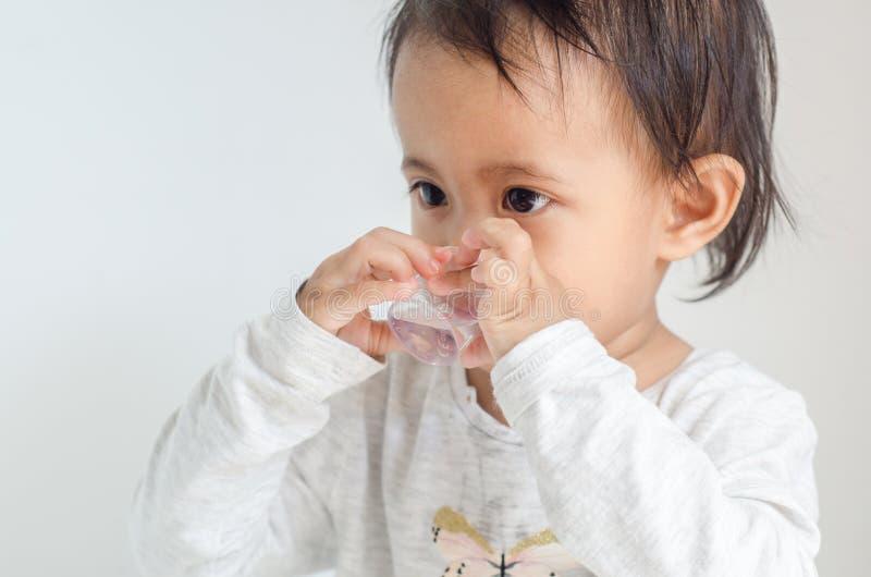 La bambina asiatica prende lo sciroppo della medicina sola fotografie stock libere da diritti