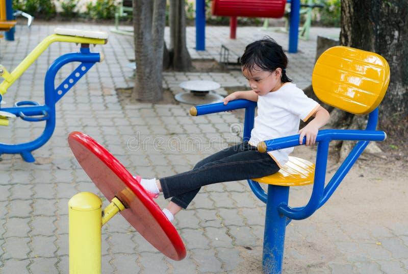 La bambina asiatica sta giocando in una palestra all'aperto fotografie stock