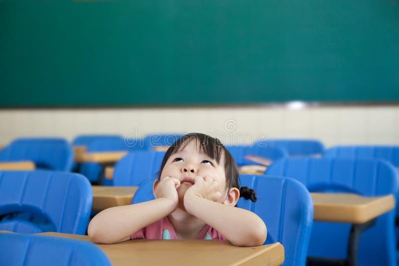 La bambina asiatica sta pensando immagini stock libere da diritti