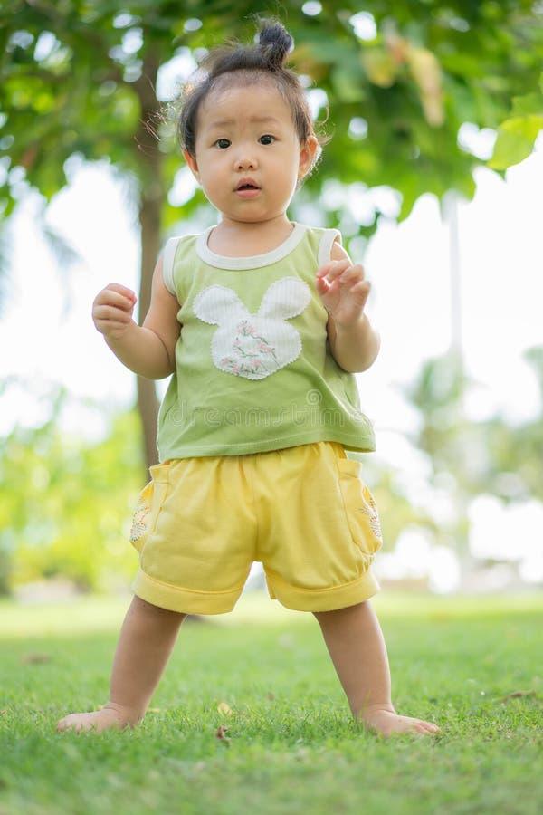 La bambina asiatica sta stando sul prato inglese al parco, La bambina impara stare, neonata con una voglia, voglia sul suo immagine stock libera da diritti