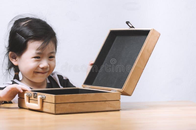 La bambina asiatica sveglia sorridente è felice di aprire una borsa del regalo con immagine stock libera da diritti