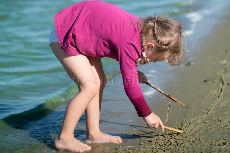 La bambina attinge la sabbia fotografia stock