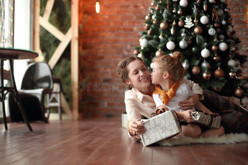 La bambina bacia sua madre vicino all'albero di Natale fotografia stock libera da diritti