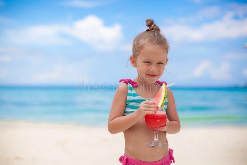 La bambina beve il succo dall'anguria sul immagine stock